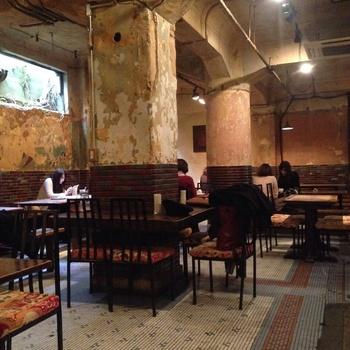 その地下1階にあるのが、『Cafe Independants(カフェアンデパンダン)』。 午前0時まで営業されていて(2016年10月現在)、カフェ使いもバー使いもできるアートなカフェです。アンティーク調の大きなテーブルやタイル張りの壁、いい感じに崩れた壁紙が作り出す雰囲気が心地よい、昼からでも心置きなくワインを飲めるお店です♪ (ちなみに、お店を出たところにあるお手洗いまでもアンティークでオシャレ)