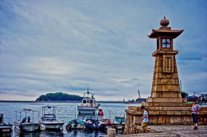 常夜灯のあるこの場所は、鞆の浦のシンボル的存在。  船着き場にはタイヤをつけた白い小さな漁船がたくさんあり、鞆の浦の風情が感じられます。 これらと同じようなデザインの漁船が、「崖の上のポニョ」の中にも出てきます。