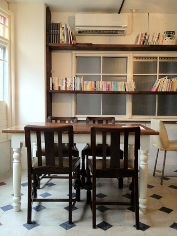 白を基調とした明るい店内の壁に、お店のセレクトした本が並びます。 テーブルの足や、床のアンティークな模様も素敵ですね。