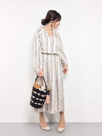 白の爽やかな小花柄ワンピースコーデには、シックなカラーの大振りイヤリングとバケツバッグを合わせて大人っぽい雰囲気に。