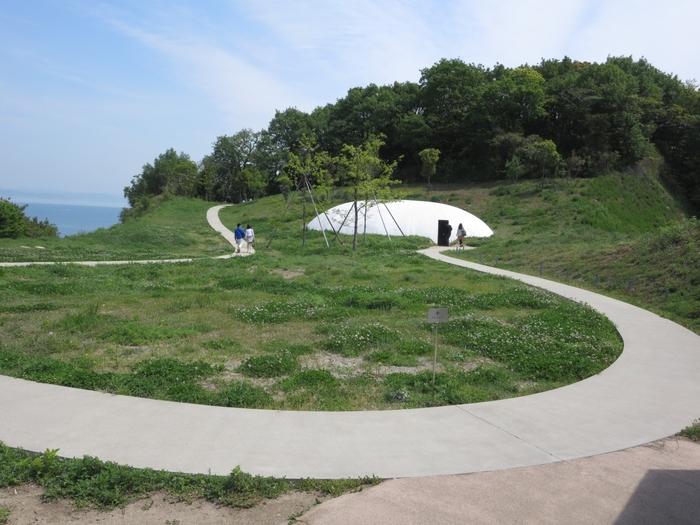 豊島美術館 (ベネッセアートサイト)/ 香川県豊島・・・瀬戸内海を望む豊島唐櫃(からと)の小高い丘に建設された「豊島美術館」。その広大な敷地の一角に水滴のような形をした建物が据えられました。内部空間では、一日を通して「泉」が誕生します。その風景は、季節の移り変わりや時間の流れとともに、無限の表情を伝えます。