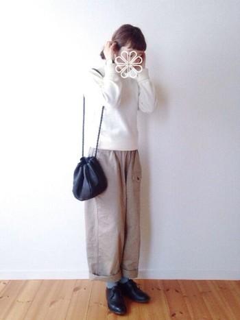 レザーの巾着は、かわいらしい中にもしっかりと大人っぽさが出ます。白のニットやベージュのワイドパンツと合わせて、リラックス感のある、柔らかなコーディネートに仕上がっています。