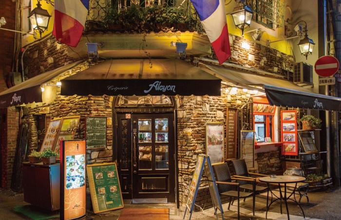 クレープリー・アルションは、戎橋筋商店街の脇道にある一軒家のカフェレストランです。フランスの国旗が掲げられているお店の外観は可愛らしく、フランスの田舎町を彷彿とさせる趣です。
