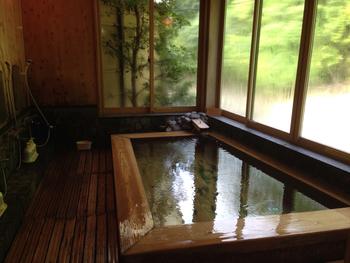 内湯は檜風呂。内湯からでも景色を楽しめます。露天風呂もあります。
