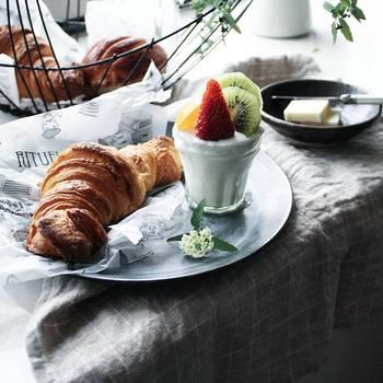 パンやバターをバスケットや小皿に別盛りにして、朝からカフェ風にテーブルコーデ。グラスに入ったヨーグルトは、フルーツの後のせがポイントです。朝から、優雅な気分を楽しめそうですね。