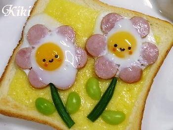 ウインナーと卵でお花を作って、のりで顔をつけた簡単トースト。下に敷いたチーズがいいアクセントになっています。これなら朝からもりもり食べてくれそうです。