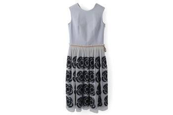 ウェスト部分で切り替えのある繊細なワンピース。チュール仕立てのスカートには、黒い糸で大胆に描かれたお花模様の刺繍が並んでいます。淡い色合いとチュールの儚げな雰囲気に、刺繍の力強さが加わって、女性の多面性をも連想させる秀逸なデザインです。