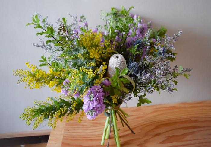 目を引く花を中心に、左にミモザの黄色、右にブルー系でまとめたナチュラルな花束。こんな花束を飾ったら、リビングが途端にオシャレになりそう。