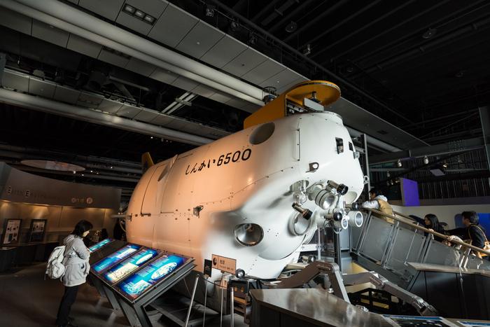 こちらが「しんかい6500」の原寸大模型。  現役で活躍中の有人潜水調査船で、水深6,500mまで潜ることができるとってもすごい潜水艦。 全長は10m弱もあるのに、人が乗れるのは直径2mの耐圧殻(コックピット)の中だけなんです。  中に入って、潜航体験だってできちゃうんですよ。 まるで深海調査研究士になった気分を味わえます。