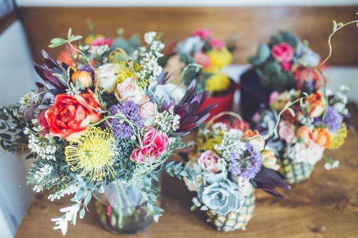カラフルな花々をまとめ上げるのは、ねず色に輝くシルバーリーフと多肉植物。パイナップル型のフラワーベースもおしゃれ。