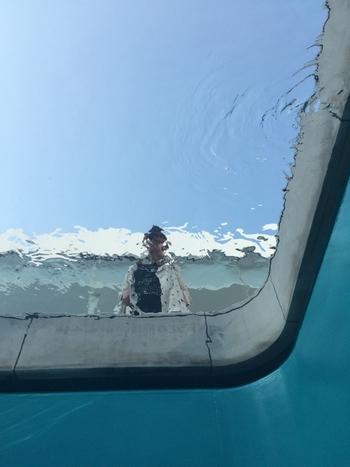 プールの中から見るとこんな感じに見えるんです。  地上から見下ろす人と地下にいる人たちが水面を境界にして出会いを創出した作品。 水を通して感じる太陽の光はとてもきれいで、こちらを覗き込んでいる観覧者を見ているうちに、まるで自分が魚になったような感覚になります。