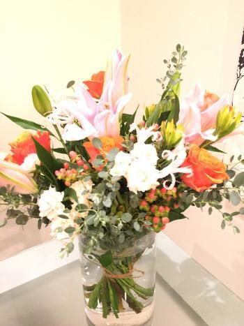 夕焼けのようなバラ、白いミニバラ、ユリをメインに、実があるものとユーカリをまとめあげた華やかなブーケ。年齢を問わず贈る方すべてに喜んでもらえそう。