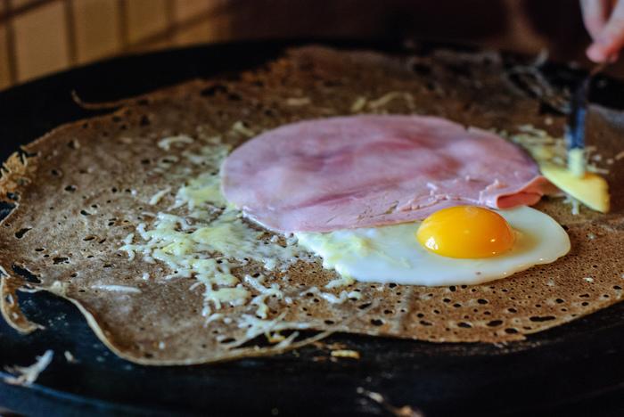 3. 大きめのフライパンを中火にかけて、熱くなったらキッチンペーパーに含ませたオリーブオイルや植物油をフライパンに塗る。 4. 大匙2~3杯くらいの少量の生地を流し入れて、すばやく全体に広げる。表面に気泡が出てきたら、スパチュラを使ってそっとひっくり返す。