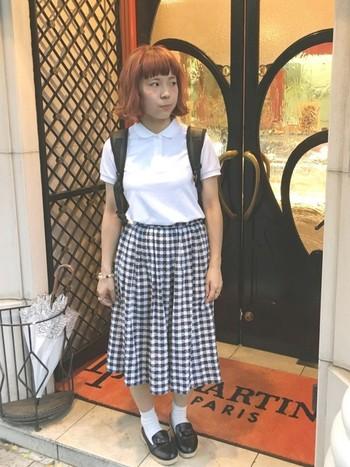 ホワイトのポロシャツに、ギンガムチェックのスカートをあわせたコーディネート。足元にはローファーでキレイめなスタイリングに。