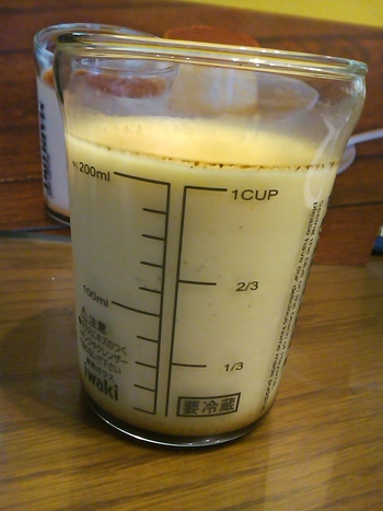 """プリンの入ったビーカーの裏面。こんな風に200mlまでの目盛りがついているので、食べ終わった後も色々使えます。しかもこのガラスはパイレックス製もしくは耐熱容器でお馴染みの""""iwaki""""製なのでレンジ使用もOKです。"""