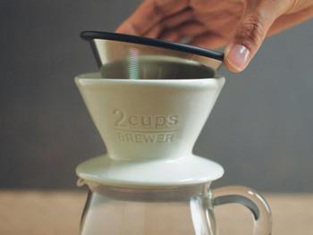 ①  ドリッパーにフィルターをセット。お好みの中挽きのコーヒーの粉を入れます。直接粉をドリップすることで、コーヒーのアロマが一層引き立つんです。