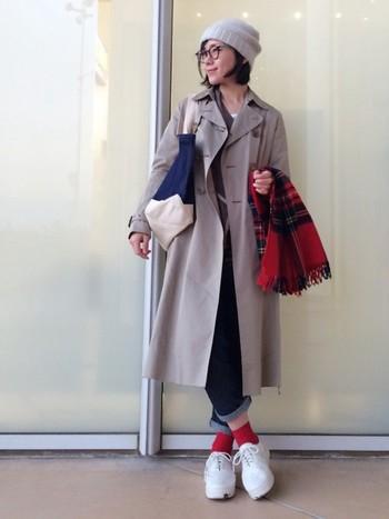 カチッとしがちなトレンチコートをニット帽とスニーカーでカジュアルダウン。ストールと靴下の赤が差し色で効いています。