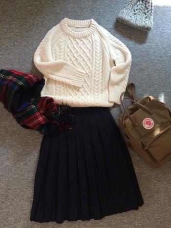 ミモレ丈のスカートにリュックを合わせて元気な印象に。ケーブルニットのトップスとニット帽に赤いストールで、温かみのある冬らしいコーデ。