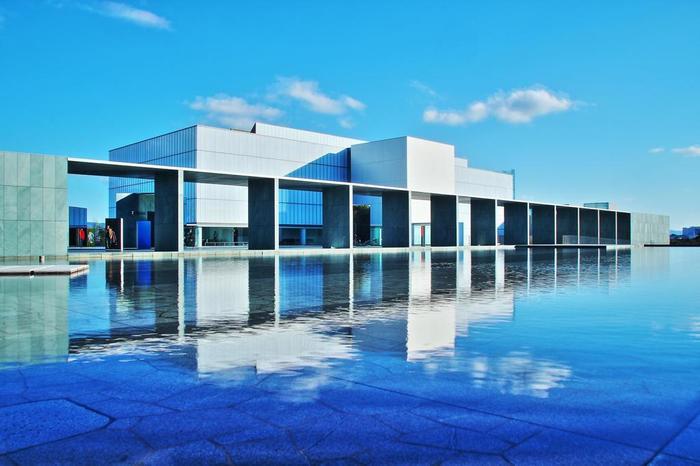 ゆったりとした広大なスペース、そして水辺。静寂という言葉が似合うような佇まいの豊田市美術館。モス・グリーンのスレートと乳白の磨りガラスで構成されたモダンな外観が特徴的。建築家、谷口吉生氏の代表作のひとつです。