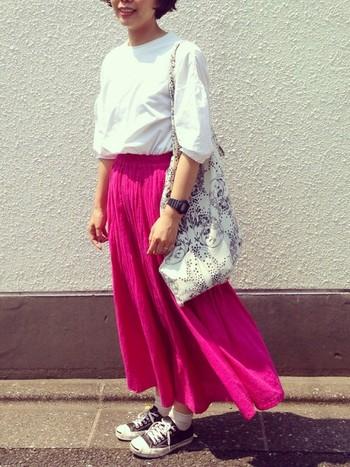 遠くからでもパッと目を引くビビッドなピンクはスカートで風を感じるコーディネートに。他のアイテムをモノトーンでまとめることで、うるさくなりません。