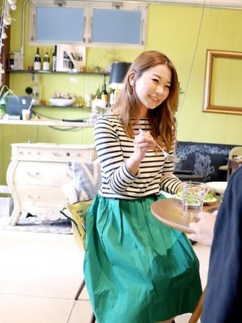 白と黒のボーダートップスには、どんな色でも合わせられます。普段はあまり着ない色に挑戦してみては?鮮やかなグリーンのスカートもぴったり合います。