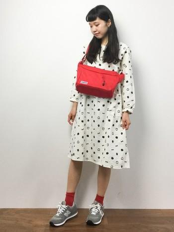 白地に黒の模様が入ったワンピースは、春には一枚でさらりと着こなしたいですよね。赤のバッグと靴下を合わせて、元気いっぱいのコーディネートに。