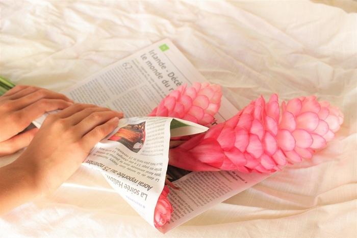 新聞紙で花首が下がったお花を巻いていきます。  注意する点は、花首を真っ直ぐに整えてから巻くこと。 そして茎の下が新聞紙から出るようにすること。