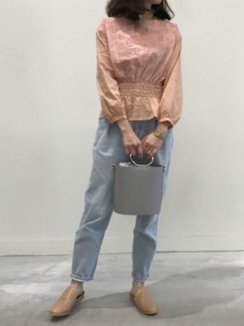 シャーリングデザインが女性らしいピンクのコットンブラウスにライトカラーのデニムを合わせた、春カラーのスタイリング。バケツバッグがより今年らしい印象にしてくれます。