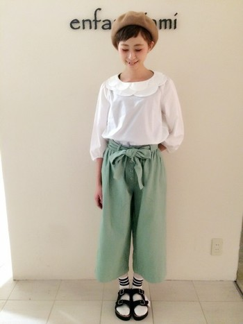 可愛らしい白ブラウスに、パステルグリーンのガウチョパンツ。甘く可愛らしい着こなしを、スポーティーな足元でちょっぴり外して。