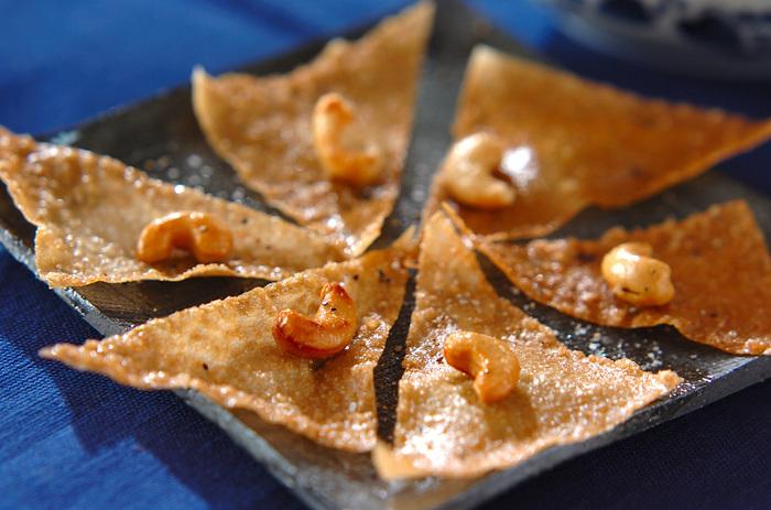 春巻きの皮をカットして揚げてシンプルに味付けしたおつまみレシピ。カシューナッツの食感や風味がアクセント!ディップと合わせても◎