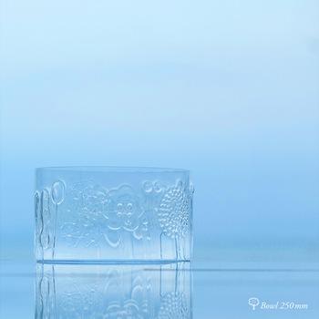"""北欧フィンランドで最も古いガラスメーカー「Nuutajarvi(ヌータヤルヴィ)」から1966年に発表されたシリーズ、「flora(フローラ)」。デザイナーOiva Toikka(オイバ・トイッカ)の代表作のひとつであるこの繊細なガラスの器は、職人がひとつひとつ""""マウスブロー(吹きガラス)""""で手がけたもので、立体的なエンボス加工でデザインされた木や花などのモチーフも愛らしく、多くのファンに支持されてきました。"""