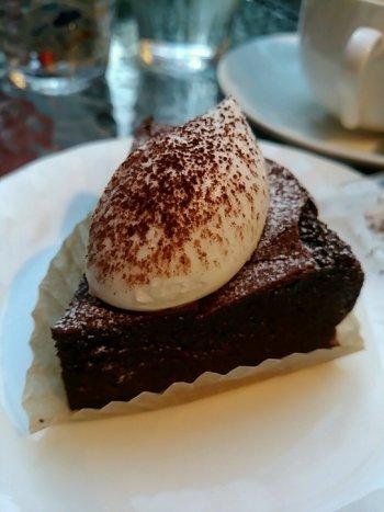 お店でいただくガトーショコラには、ほどよい甘さの生クリームがのせられ、より上品な味わいになります。コーヒーと一緒に食べるのがおすすめ。