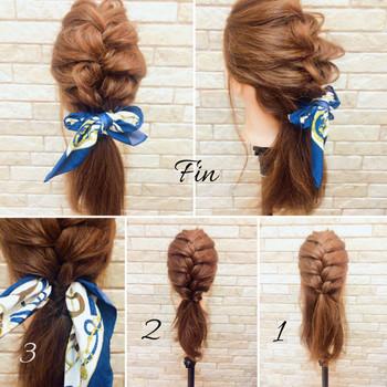 耳の下までざっくり大きく編み込みをした後、残った髪の毛と一緒にまとめ、スカーフでとめたスタイル。洋服に合わせてスカーフも変えられ、色々楽しめるスタイルです。ゴムとゴムの間にスカーフを通してリボン結びにする方法なので、風が吹いても崩れにくいスタイルです。