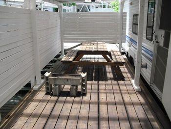 トレーラーハウスは屋根のついたウッドデッキに横付けされ、テーブルや椅子、火をおこすU字溝などが完備されています。