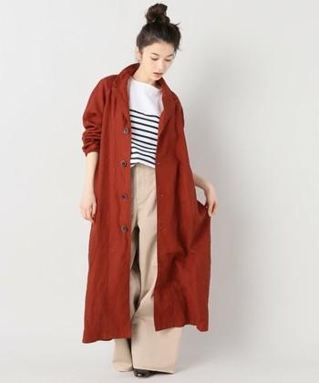 テラコッタカラーのコートにベージュのバギーパンツが新鮮なシルエット。ヘアスタイルは無造作にまとめています。