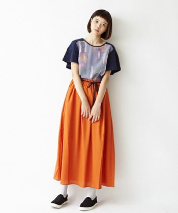 シンプルなTシャツにも、アートな柄をとりいれることで存在感もUP!柄に使われているオレンジをボトムスにあわせて、ワンランク上の着こなしに。