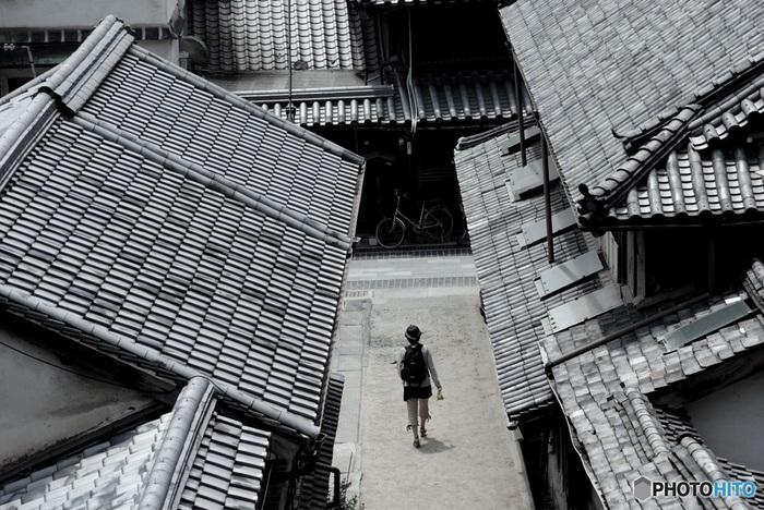 """全国には「町並み保存地区」が数々ありますが、ここ竹原の町並みは切妻屋根や入母屋造りの屋根等、様々な建築様式が混在しているため変化に富み、落ち着いた中にも他所にはない独特の趣きがあります。  散策のメインは、保存地区を貫く""""本町通り""""ですが、小路も風情ある雰囲気。地区内に足を踏み入れれば、時が経つのを忘れてしまうはずです。"""