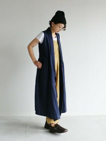 マキシ丈のワンピースを羽織りとしてあわせたコーディネート。ニット帽をあわせて、縦のシルエットを上手く活用できています。