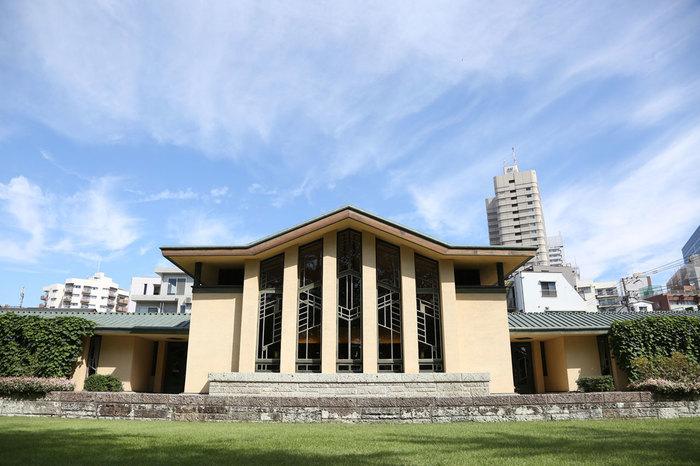 """フランク・ロイド・ライト氏はアメリカ出身の建築家で、低い屋根が水平に長く伸びる""""プレーリースタイル(草原様式)""""の確立の最大の立役者であり、91歳の生涯を閉じるまで、約400の作品を世界的に手がけたと言われています。そのライト氏が初めて学校建築に挑んだのがこの校舎。コの字型をした左右シンメトリーの建物は、平等院鳳凰堂に影響を受けたと言われており、広々とした庭園と調和して、開放的な空間が広がっています。"""