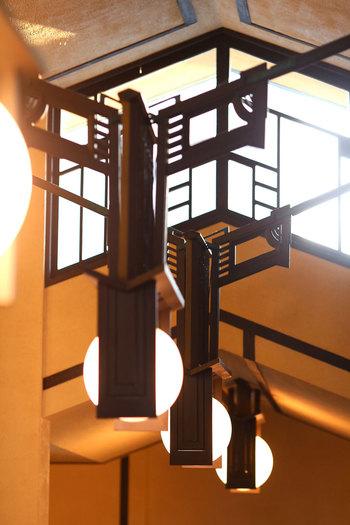 満月を思わせる照明もライト氏オリジナルのもの。90年以上も前のデザインとは思えないほどおしゃれで古さをまったく感じません。また、屋根と同じ緩やかな勾配を持つ天井を持っていますが、この三角形の角度は明日館のあらゆる装飾の基準に。窓の幾何学線や照明の飾りも天井と同じ角度の線の組み合わせでできており、建物全体が同じ角度で統一されています。
