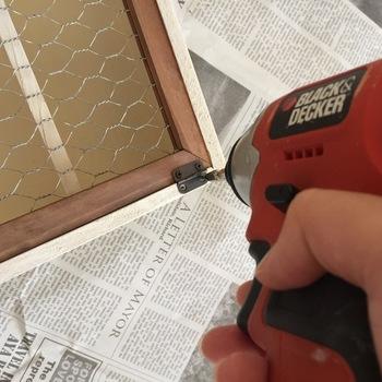 背板を横31.5×縦21.5cmにカットしてボンドとタッカーで背面に取り付け、全体に塗料を塗って乾かします。次にインテリアメッシュフレームの方に蝶番を付け、本体に固定したら完成です。蝶番は先にフレームの方から付けておくと、固定しやすいですよ☆