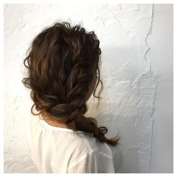 顔周りの髪をねじってからロープ編みでまとめて、さらに横に流しています。髪をしっかりめにカールさせることで外国人風のアレンジに。