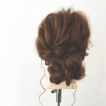 髪を左右ふたつに分け、それぞれをくるりんぱしてから三つ編みにし、毛先を内側に丸めてUピンで固定したシニヨン風スタイルです。分け目を見せず、ふんわり崩すといい感じ♪