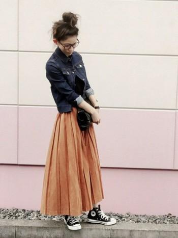 長め丈のキャメルのプリーツスカートに、コンパクトなGジャンを合わせてカジュアルダウン。クラッチバッグには黒を選べば、全体的に引き締まった印象になります。