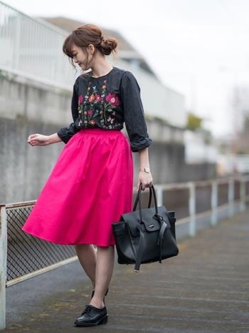 人気の刺繍アイテムには、より鮮やかで人目を引きつけるピンクのスカートを合わせて。ブラックのアイテムでまとめて、ピンク色を引き立てて。