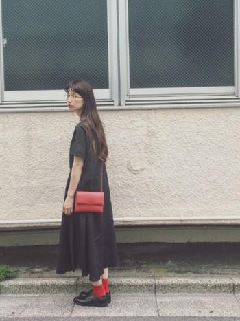 赤の靴下と黒の革靴は、なんだかトラッドで粋な組み合わせですよね。ベーシックな黒のワンピースに、靴下とバッグ、ダブルの差し色アイテムを使っています。センスの光るコーディネートです。