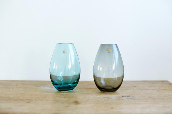 """世界中の""""素敵""""をセレクトしたお店「SUU」から、デンマーク王室御用達ブランド「HOLMEGAARD(ホルムガード)」の花器が届きました。 """"Master of Light""""と呼ばれるガラス作家、ピーター・スヴェアが「雫」をモチーフにデザインしたCOCOON(コクーン)シリーズ。控えめな色が光を捉えてフォルムをより生き生きとさせるように計算されています。一見シンプルな形ですが、ガラスで""""自然""""の美しさを導き出し、製品化されるまでには長い年月がかかったそう。  機能性においても、口が大きく丸みのある形は安定感もあり、1輪でもボリュームのある花束でも大丈夫。花の種類を問わず綺麗に生けることができます。  今回は日常使いしやすい高さ17cmと小さめのサイズに、ナチュラルなインテリアにも合わせやすい「アクア」と「スモーク」の2色をご用意しました。この2色は、SUUの別注で実現した限定カラーです。"""