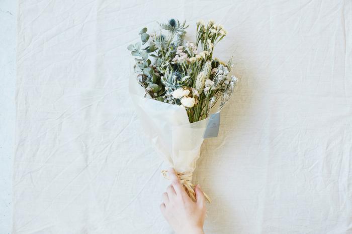 可憐な花、小さな野の花、良い香りのハーブ、淡いグリーンなどを束ねたドライフラワーの花束を、フラワーショップ「ex.(イクス)」がご用意しました。 東京・中目黒と蔵前にある小さなお店には生き生きとした季節の花や緑がたくさん。また「植物を活かしきること」をモットーに、ドライフラワー作りにもこだわりがあります。  ドライフラワーは水遣りがいらないので、吊るしたり置いたり、飾り方は自由自在。 でも花束のボリュームをそのまま楽しむなら、花器に生けるのがおすすめです。