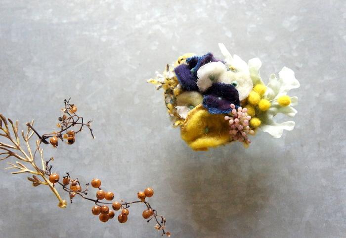 カラフルなお花を束ねたブローチは、装いに華やかさをプラスしてくれますね。ディテールにまでこだわりが感じられます。