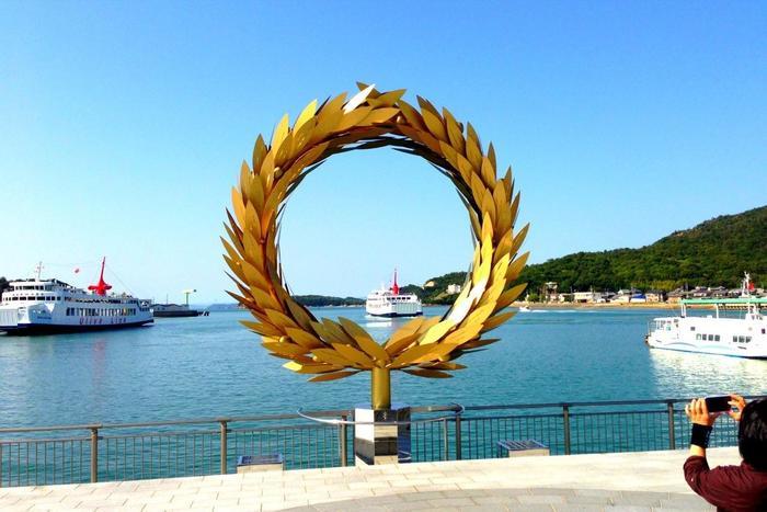 小豆島の玄関口の港に設置されている、崔正化(チェ・ジョンファ)の「太陽の贈り物」。  金色に輝くオリーブの円環からは、瀬戸内に素晴らしい景色が眺められます。